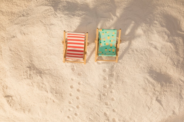 Small colorful deckchairs and footprints on sand