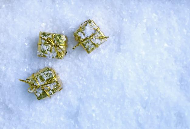 ふわふわの雪の上の小さなカラフルな金色のギフトボックス。冬のデザイン要素。