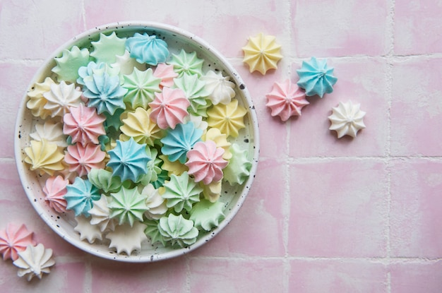 Small colorful meringues in the  ceramic bowl on pink tile background