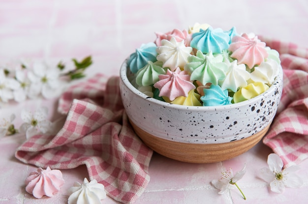 Small colorful meringues in the ceramic bowl on tile background