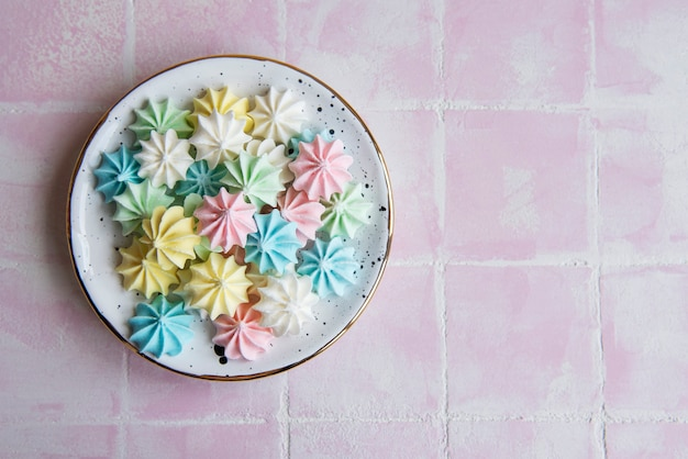 Small colorful meringues in the  ceramic plate on pink tile background
