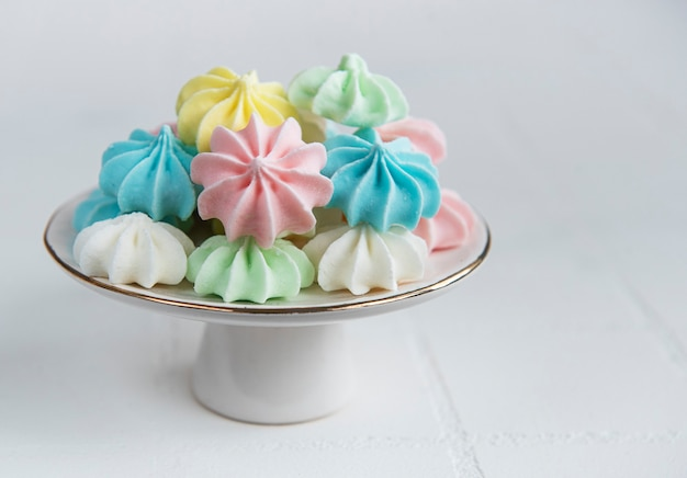 Small colorful meringues on the ceramic  stand on tile background