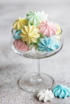 Small colorful meringues in the  glass on concrete background