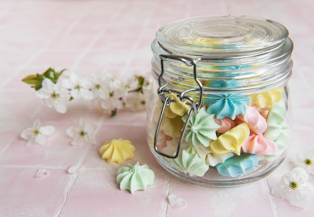 Small colorful meringues in the  glass jar on pink tile background