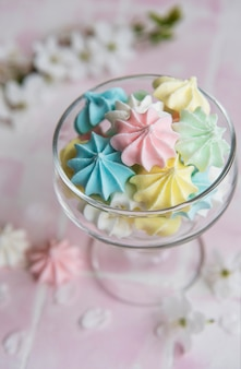 Small colorful meringues in the  glass on pink tile  background
