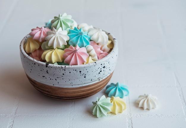 Маленькие красочные безе в керамической миске на фоне плитки