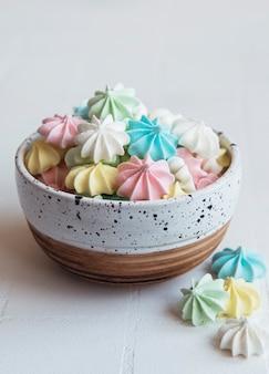 타일 배경에 세라믹 그릇에 작은 다채로운 머랭