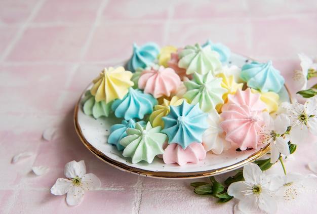 Маленькие красочные безе в керамической тарелке на фоне розовой плитки