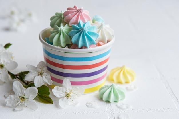 Маленькие красочные безе в бумажной миске на фоне плитки