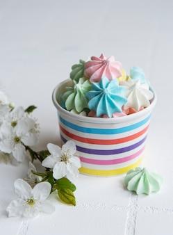 타일 배경에 있는 종이 그릇에 작은 다채로운 머랭