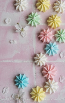 Small colorful meringues  on pink tile background