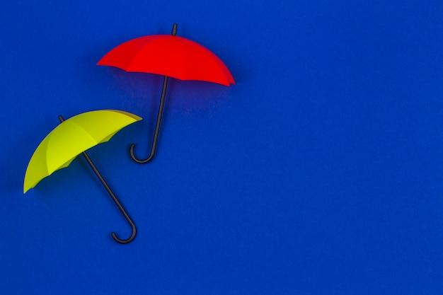Small colorful umbrellas on blue color
