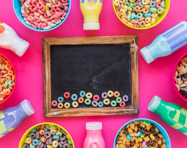 Small colourful cereals on chalkboard on table
