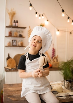 A small cook boy in a cap and apron sits on table in the kitchen and holds wooden spoons