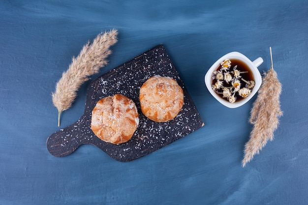 Маленькие профитроли печенья с сахарной пудрой и палочками корицы.