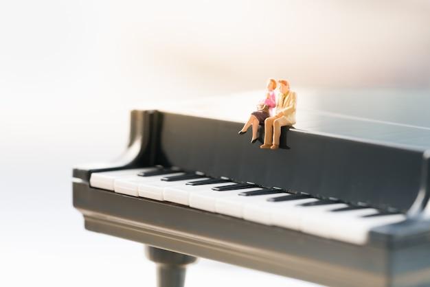 Small couple figure sitting on mini piano.