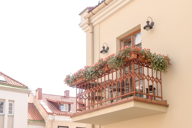 Small cozy balcony with outdoor furniture lighting and flowers