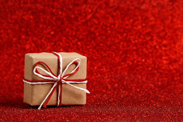 A small craft gift on a red shiny, sequins in the side. the concept for valentine's day.