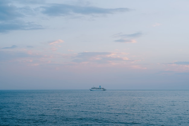 A small cruise liner sails in the open sea against the sunset sky with orange clouds