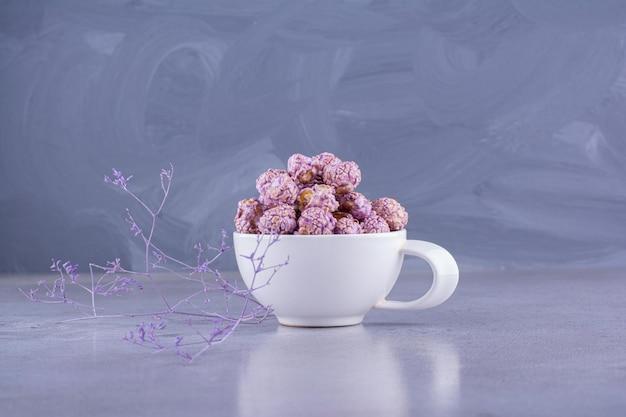 Piccola tazza di caramelle popcorn su sfondo marmo. foto di alta qualità