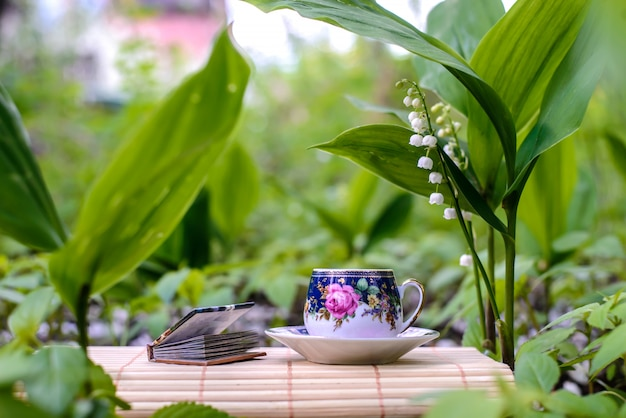 A small cup of tea next to the flowers of lilies of the valley