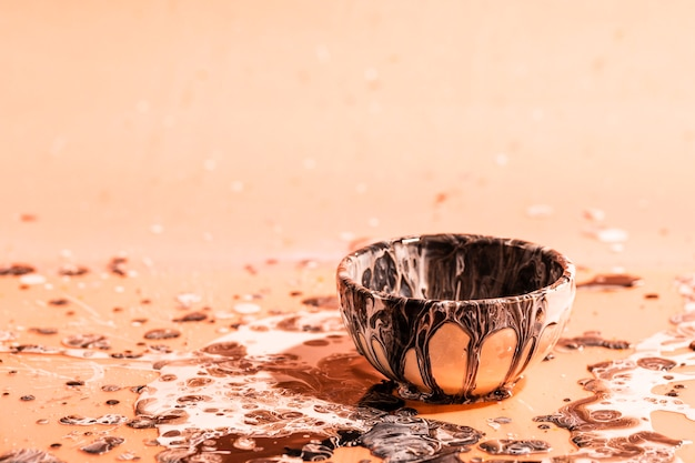 Small cup with brown paint abstract background