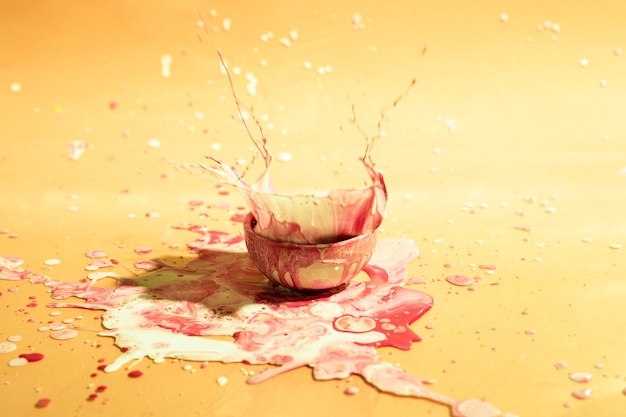 Small cup with mixed paint abstract background
