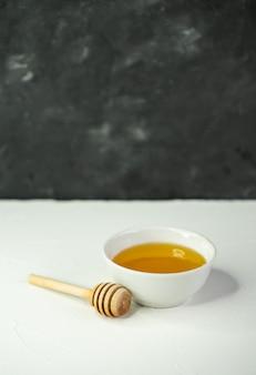 自然な蜂蜜とスプーンの小さなカップ