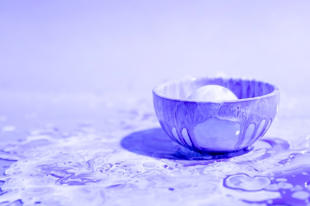 Small cup with purple paint abstract background