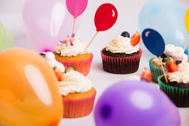 Small cupcakes with air balloons on light table