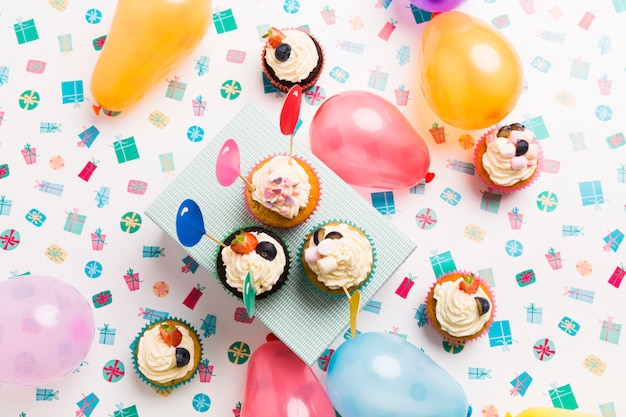 Small cupcakes with balloons on table