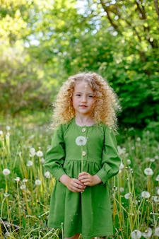 A small curly haired blonde girl blows on dandelions in a clearing