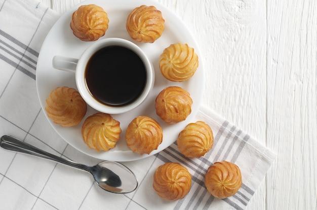 Маленькие заварные пирожные и чашка кофе на белом деревянном столе