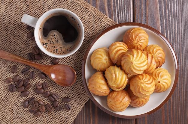 プレートと木製のテーブルの上にコーヒーを1杯の小さなカスタードケーキ