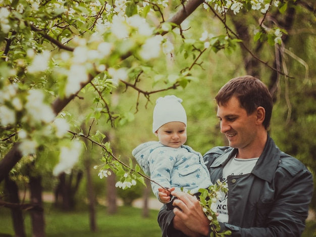Small cute baby boy with his father walking in spring park outdoor. man hold his little son on hands.
