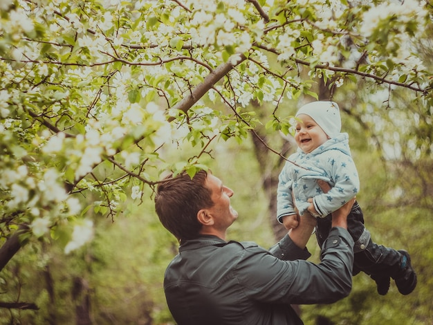 Small cute baby boy with his father walking in spring park outdoor. man raises his little son on his hands.