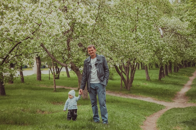 Small cute baby boy with his father walking in spring park outdoor.
