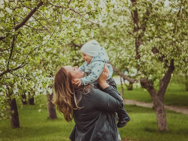 Маленький милый мальчик с его матерью, прогулки в весеннем парке на открытом воздухе. мама поднимает маленького сына на руки.