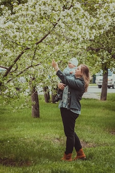 Small cute baby boy with his mother walking in spring park outdoor. mom hold her little son on her hands.