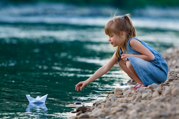 Small cute blond long-haired girl in blue dress on riverbank pebbles playing with white paper origami boat on blue sparkling bokeh water background.