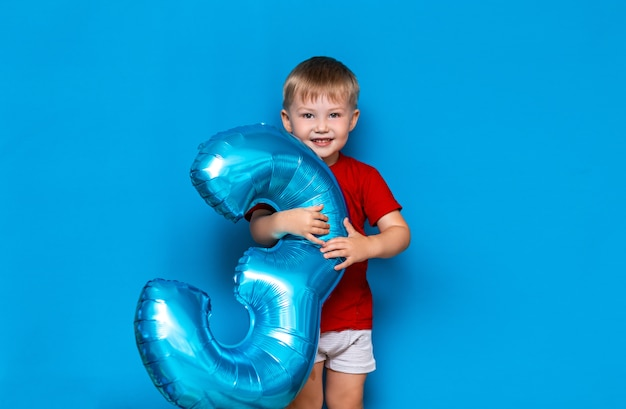Small cute blonde boy holding foil-coated sphere balloon blue color. happy birthday three years old