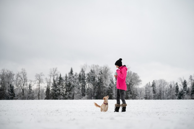 Small cute dog attentively looking at her female owner during an obedience training outside in a snowy nature.