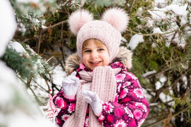 雪に覆われたモミの木の近くのピンクの小さなかわいい女性の子供