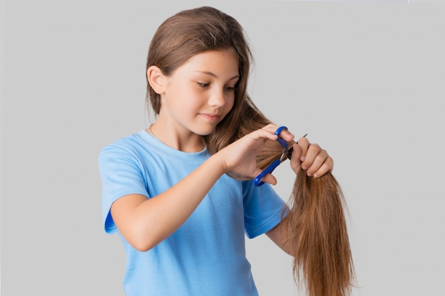 Small cute girl in blue t-shirt looking at her natural long hair and going to cut it off with blue scissors