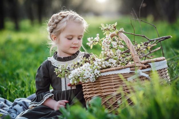 Маленькая милая девушка в платье в цветущем саду. милая девочка 3-4 лет с цветами в руках над природой. весенний портрет. ароматические цветы и ретро винтаж концепция.