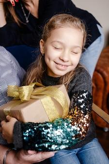 그녀의 크리스마스 선물을 껴안고 작은 귀여운 행복 소녀. 그녀의 선물 포장을 풀고 흥분된 아이