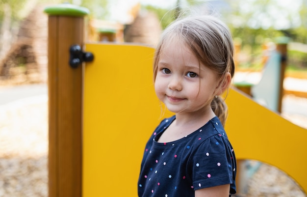 Small cute nursery school girl standing outdoors on playground, looking at camera.