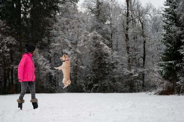 눈 덮인 자연 속에서 그녀의 주인을 향해 점프하는 작은 귀여운 애완견.