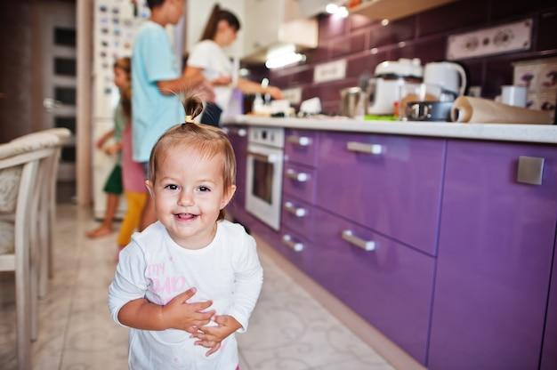 キッチンの小さなかわい子ちゃんの女の赤ちゃん。母と料理。