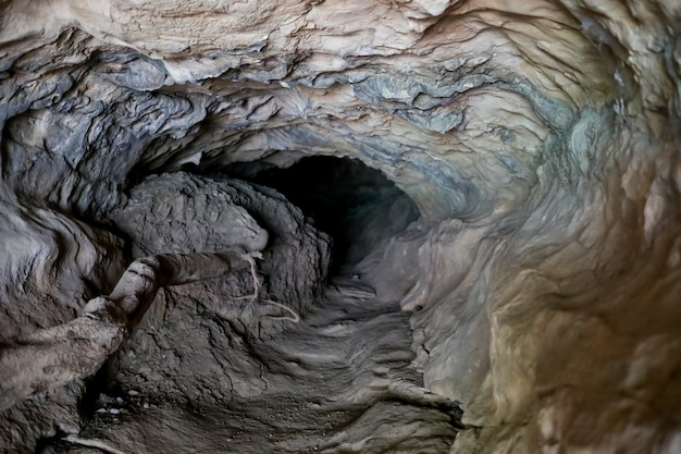Small dark grotto in layered rock formation. selective focus.